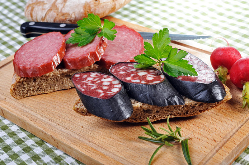 Snack bread with smoked sausages. Tyrolean rye bread with smoked sausages, decorated by red radish, parsley and rosemary stock photo