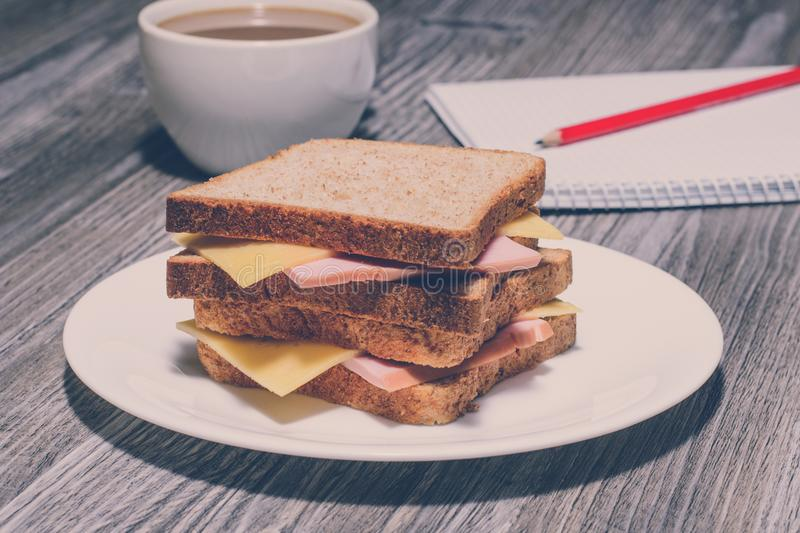 Snack education fast junk food concept. Business lunch. Tasty ham sandwich with cup of tea, notebook and a pencil. Vintage effect, stock photos