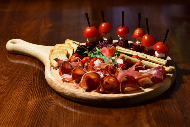 Snack food. Meat and canape on wooden board in snack counter. Chase the flavors royalty free stock photos