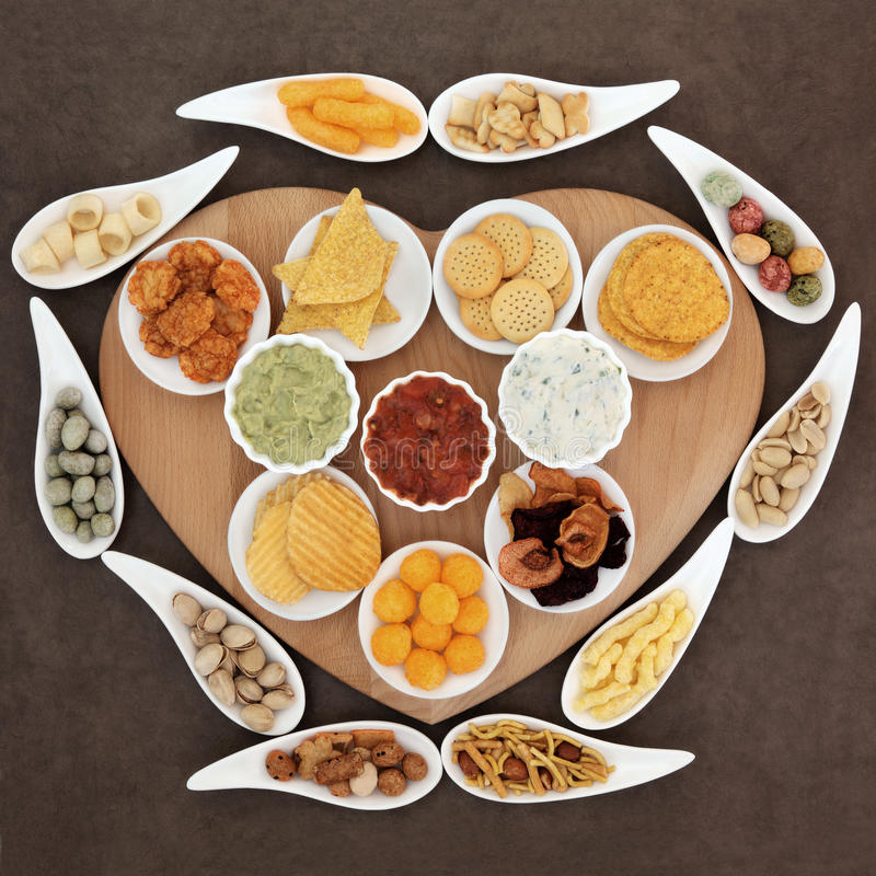 Snack Food Platter. Savoury snack and dip party food selection in porcelain dishes on a heart shaped wooden board stock photography