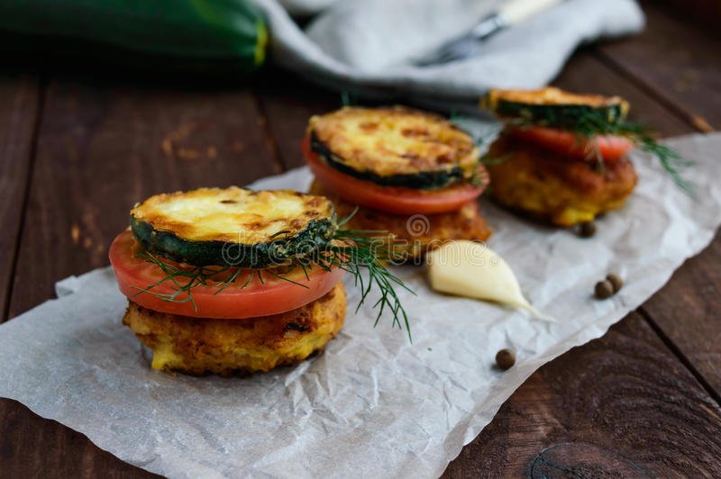 Snack in the form of a sandwich cutlet, fried zucchini, fresh tomatoes and greens. royalty free stock photo
