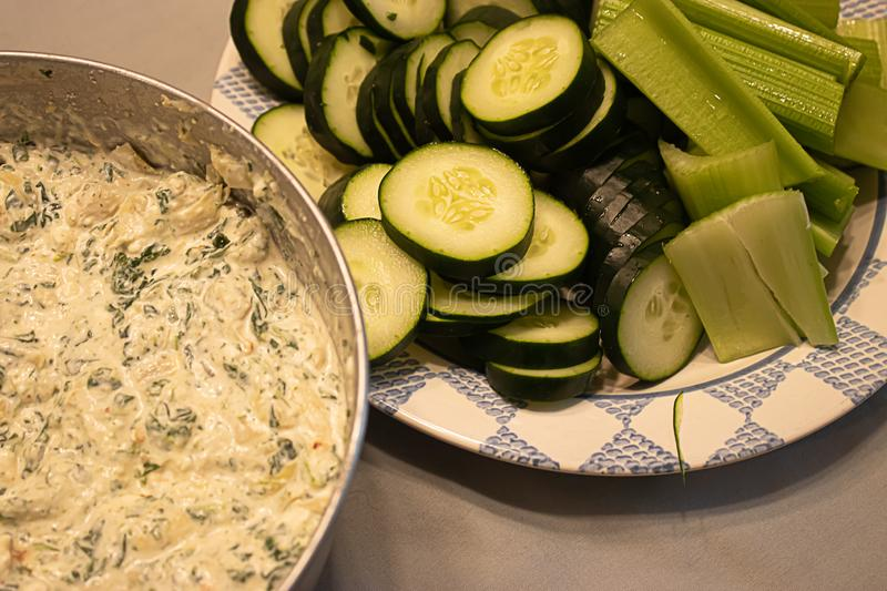 Snack of fresh spinich dip near plate of green vegetables on table royalty free stock image