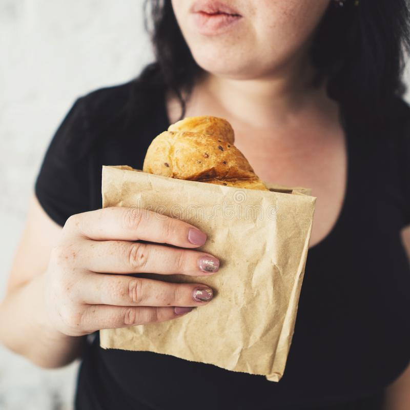Overweight woman hesitating to eat croissant royalty free stock photo