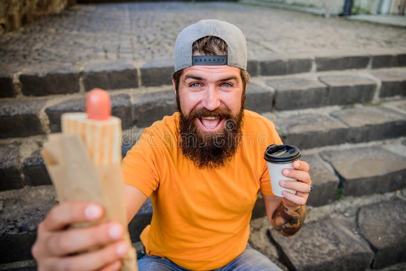 Snack for good mood. Guy eating hot dog. Man bearded eat tasty sausage and drink paper cup. Street food concept. Urban. Lifestyle nutrition. Junk food. Carefree royalty free stock photography