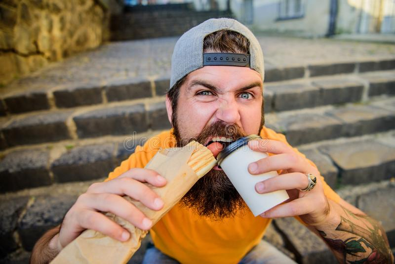 Snack for good mood. Guy eating hot dog. Street food concept. Man bearded eat tasty sausage and drink paper cup. Urban. Lifestyle nutrition. Junk food. Carefree royalty free stock images