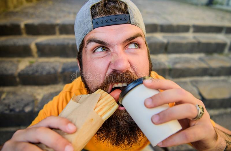 Snack for good mood. Street food concept. Man bearded eat tasty sausage and drink paper cup. Urban lifestyle nutrition. Junk food. Carefree hipster eat junk royalty free stock image