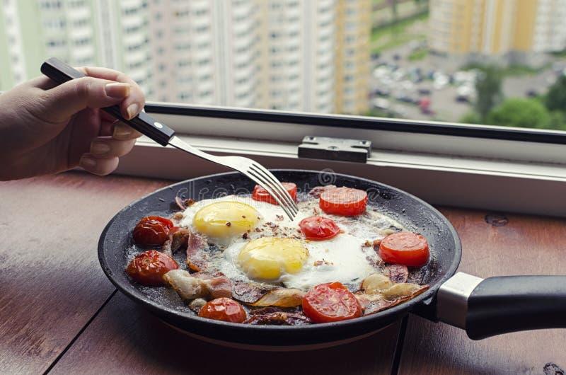 Snack met een mening van het venster, gebraden eieren met bacon en tomaten op een pan, een vrouwelijke hand die een vork over het stock afbeeldingen