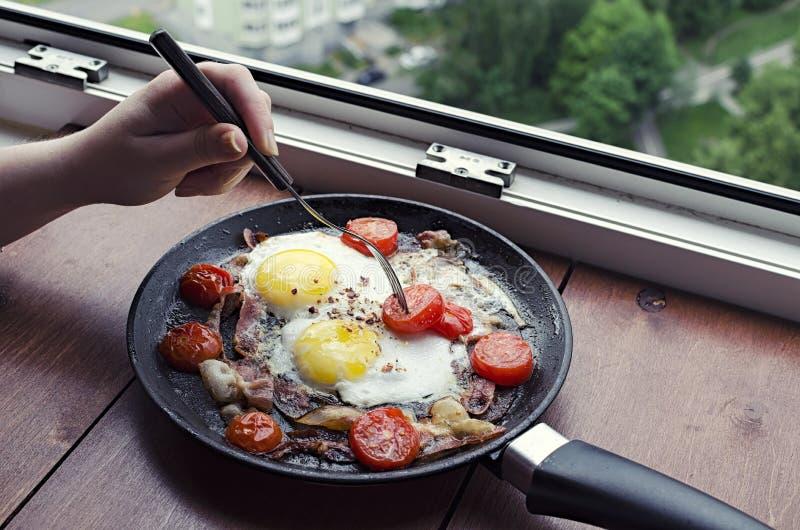 Snack met een mening van het venster, gebraden eieren met bacon en tomaten op een pan, een vrouwelijke hand die een vork over het royalty-vrije stock foto
