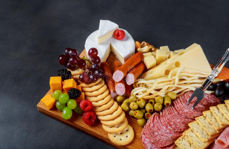Snack set with various meat variety, cheese, crackers, green olives, nuts and berries over rustic wooden table background royalty free stock image
