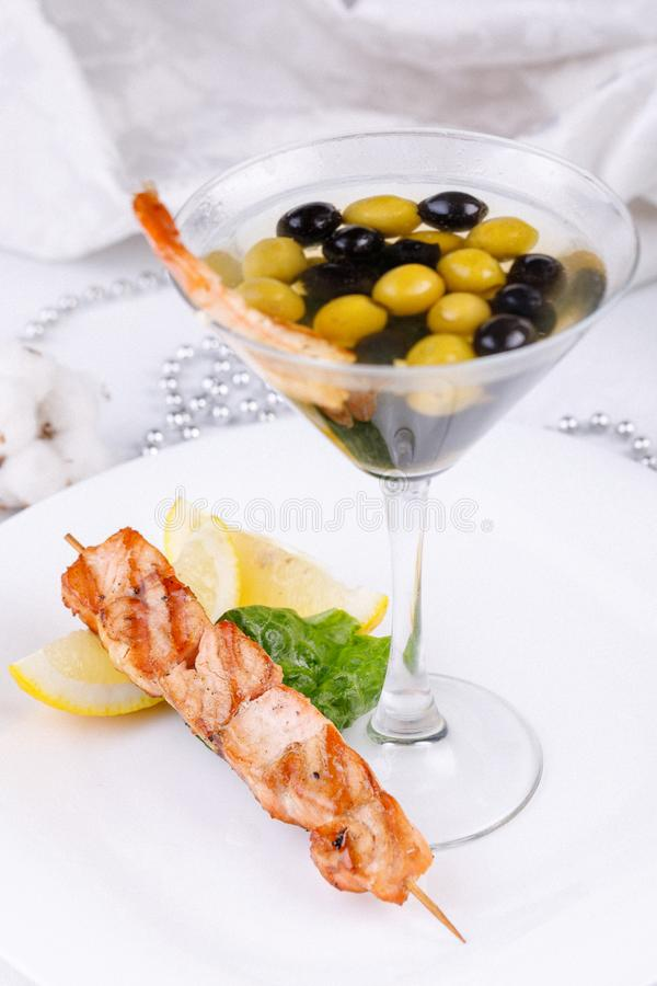 Snack from shrimps and fish shish kebab with original serving of olives in an elegant glass. Cold snack from shrimps and fish shish kebab with original serving stock images
