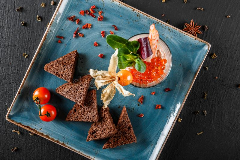 Snack from shrimps and red caviar with black bread, decorated with physalis and greens on plate over black background.Healthy food royalty free stock photos