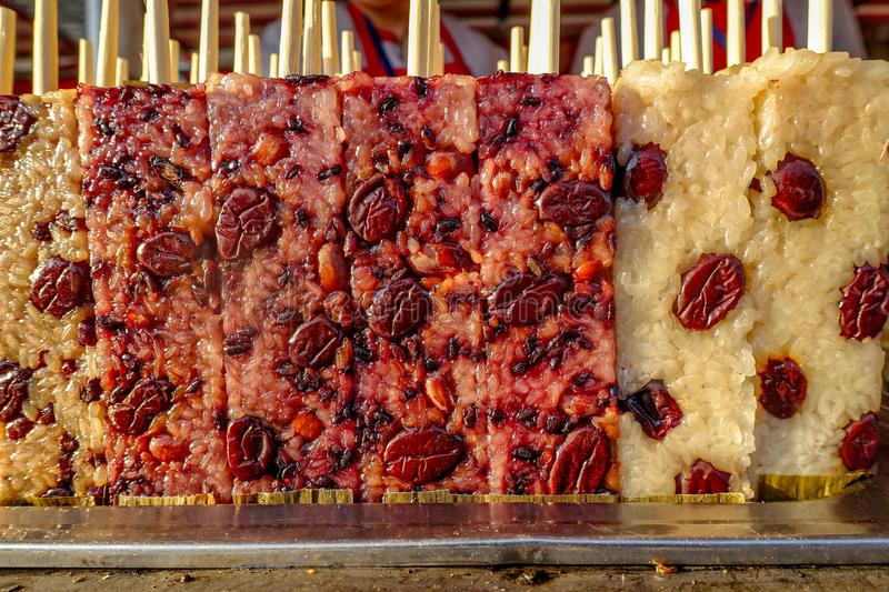 Snack Street in Beijing China. Famous Beijing street food glutinous rice stick, cooked rectangle purple rice cake. stock photos