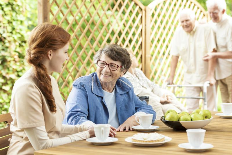 Snack time with the elderly on the patio of a nursing home. Volunteer lady talking to a senior woman sitting by a table. Two men. Snack time with the elderly on stock photo
