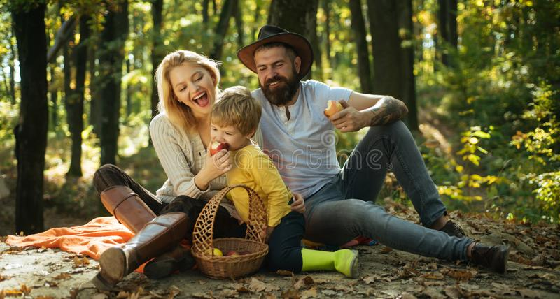 Snack time. Happy family with kid boy relaxing while hiking in forest. Basket picnic healthy food snacks fruits. Mother stock photos