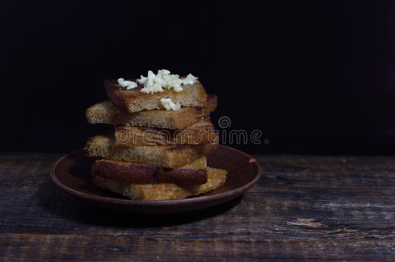 Snack from toast. Sandwich from toasts with garlic. Dark mood, Copy space royalty free stock photo