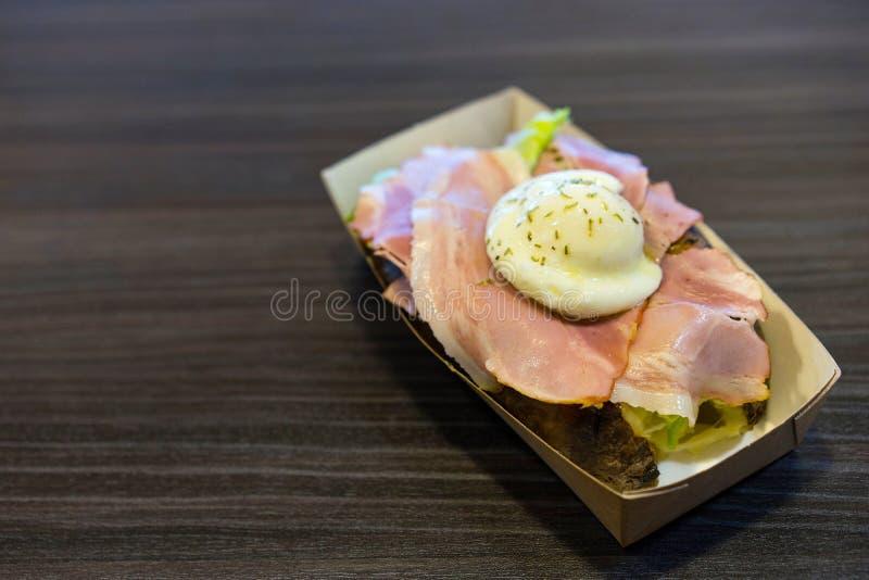 Snack van aardappelen in de schil, bacon en gestroopte eieren in een kartonvakje op een zwarte lijst royalty-vrije stock foto
