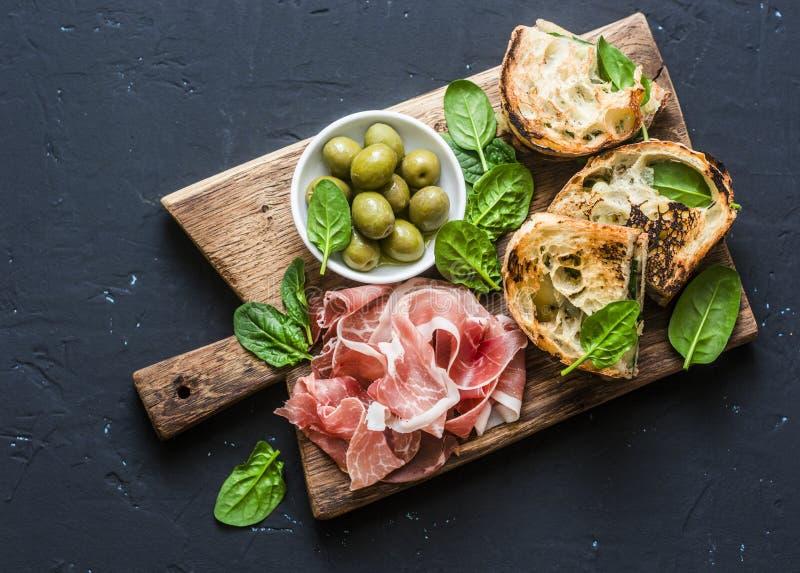 Snackbrett - Prosciutto, Oliven, grillte Mozzarellaspinatssandwiche auf dunklem Hintergrund, Draufsicht Mittelmeerartsnack, a stockfoto