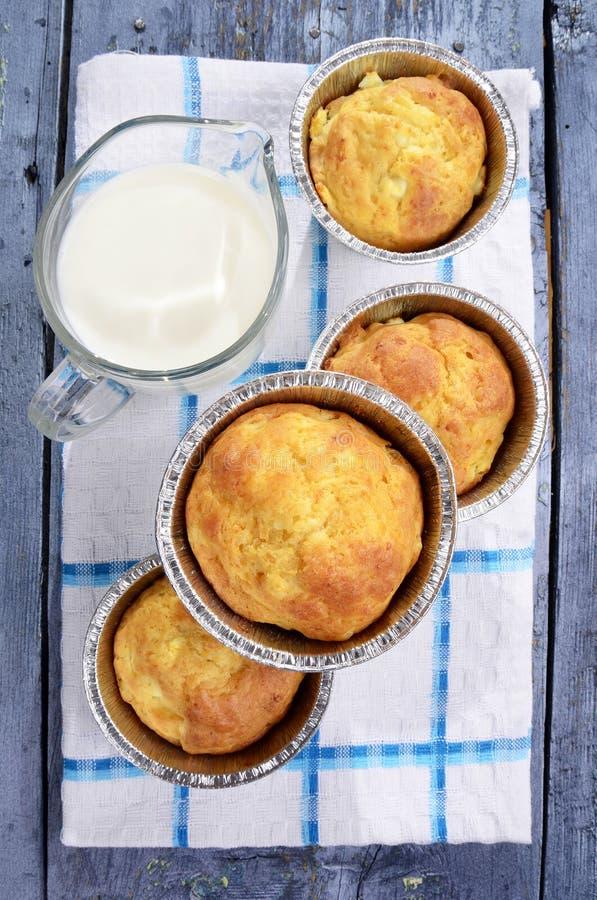 Snackmuffins, salziger Snack backt Muffins mit Käse auf einer hölzernen Platte, ein Glas frische Milch zusammen lizenzfreie stockfotos