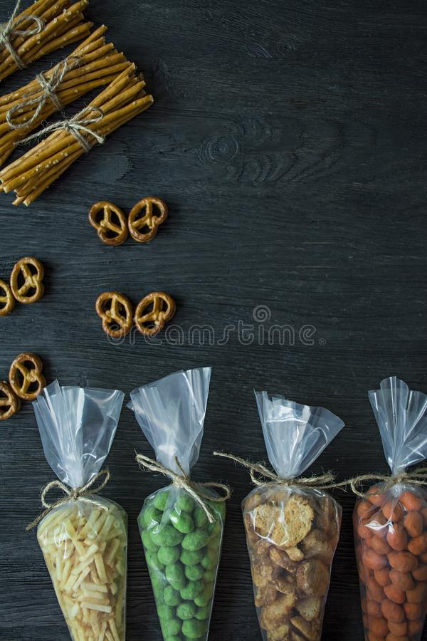 Snacks for beer. Set for beer. Nuts, crackers, fried potatoes in strips. View from above. Space for text. Dark wooden background stock image