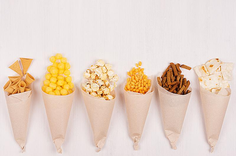 Snacks collection in craft paper cornets on white wooden board, top view, border. stock photography