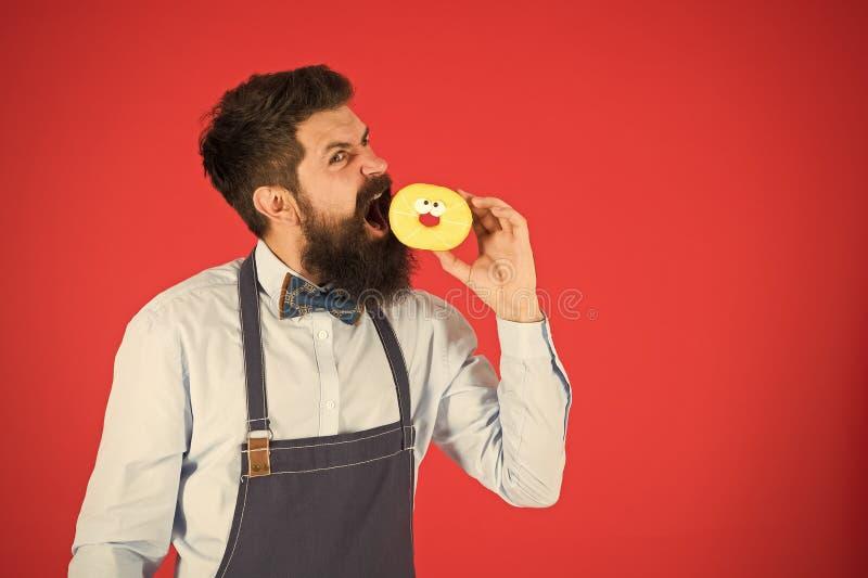 Snacks Ernährung und gesunde Ernährung Bäcker essen Donuts Köchin im Café Kalorie Hunger fühlen Bärenbäcker gebärdet lizenzfreies stockfoto