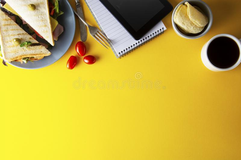 Snacks, fast food concept. Eatting at work place. Fresh club sandwich, vegetables, coffee, potato chips, sweet cookies. Tablet. Snacks, fast food concept royalty free stock photography
