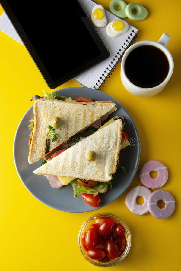 Snacks, fast food concept. Eatting at work place. Fresh club sandwich, vegetables, coffee, potato chips, sweet cookies. Tablet royalty free stock photography