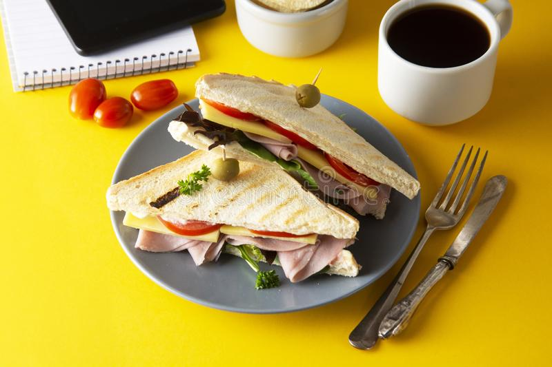 Snacks, fast food concept. Eatting at work place. Fresh club sandwich, vegetables, coffee, potato chips, sweet cookies. Tablet royalty free stock image