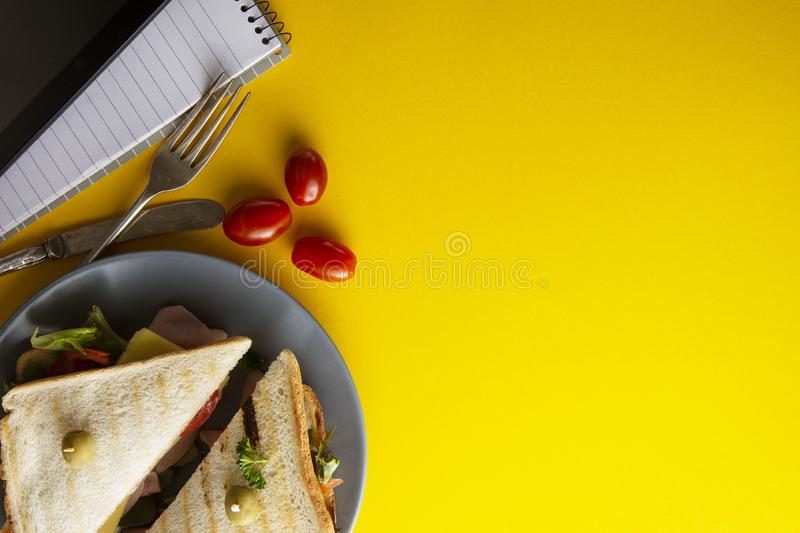 Snacks, fast food concept. Eatting at work place. Fresh club sandwich, vegetables, coffee, potato chips, sweet cookies. Tablet. Snacks, fast food concept stock image