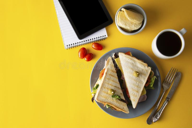 Snacks, fast food concept. Eatting at work place. Fresh club sandwich, vegetables, coffee, potato chips, sweet cookies. Tablet. Snacks, fast food concept royalty free stock images