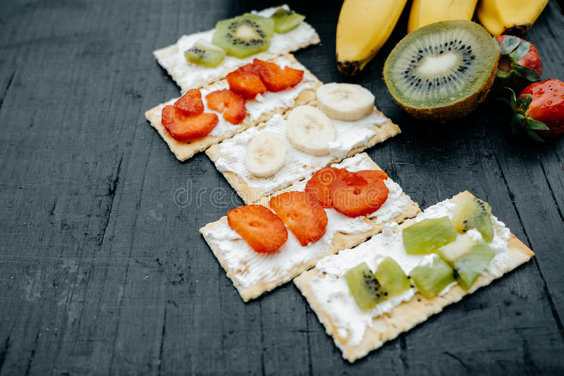 Snacks on a handmade Crackers with cheese and fruits: bananas, s. Trawberries and kiwi on a black background royalty free stock photo