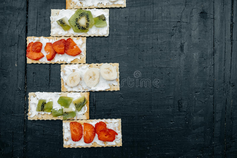 Snacks on a handmade Crackers with cheese and fruits: bananas, s. Trawberries and kiwi on a black background royalty free stock photography