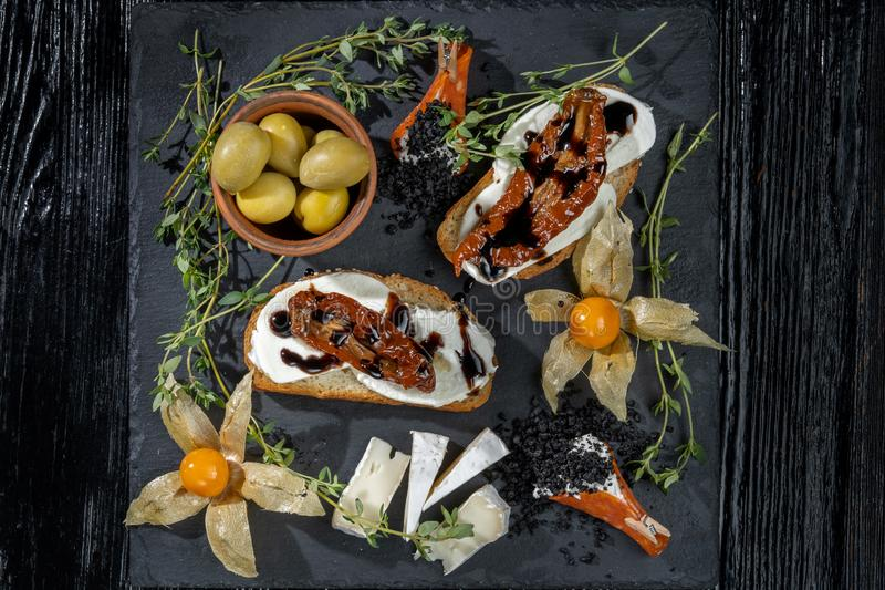 Snacks are laid out on black slate, physalis, salami, cheese and sun-dried tomatoes. royalty free stock photos