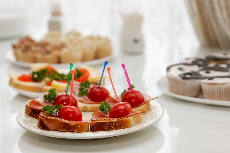 Snacks for refreshments. Sandwiches with cherry tomatoes, cakes and other snacks at the reception stock image