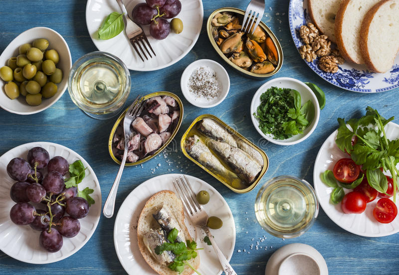 Snacks table - canned sardines, mussels, octopus, grape, olives, tomato and two glasses white wine on wooden table, top view. Flat lay stock photo