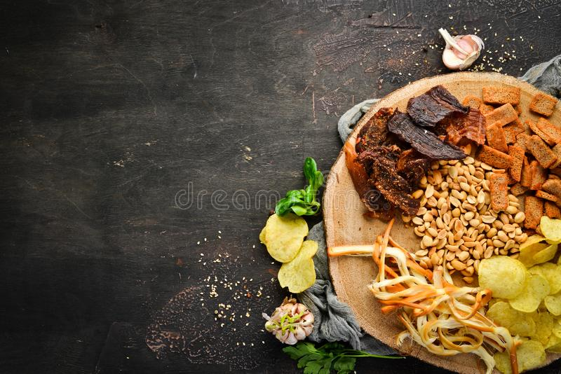 Snacks to beer. Chips, salted nuts, dried fish meat. On the old background. free copying space stock photography