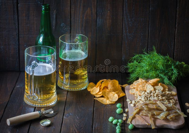 Snacks to beer, on a wooden board and two mugs of beer.Chips, peanuts, pieces of fish,crackers, dill, bottle.Copy space. royalty free stock photo