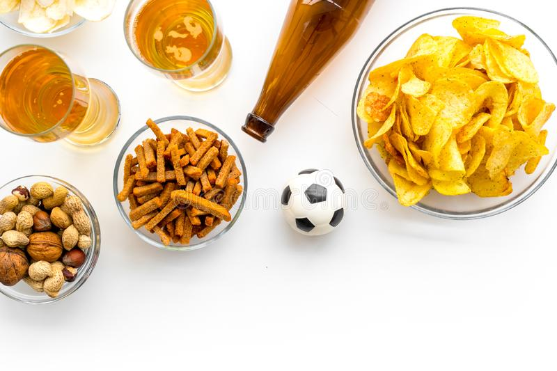 Snacks for watching football on TV. Watching sports. Chips, nuts, rusks near beer and soccer ball on white background stock photos