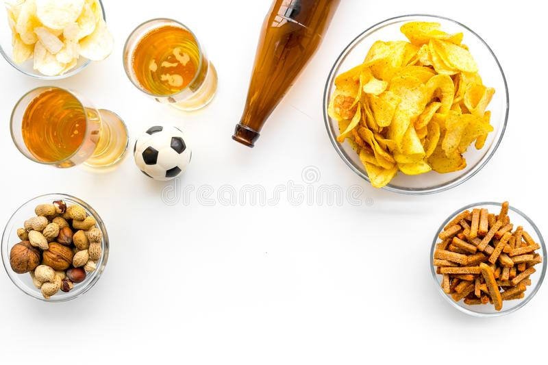 Snacks for watching football on TV. Watching sports. Chips, nuts, rusks near beer and soccer ball on white background royalty free stock photography