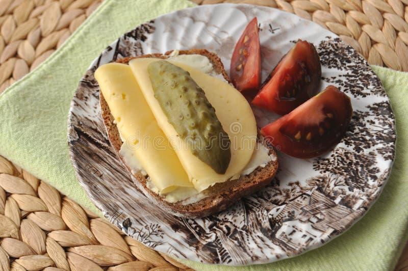 Snackvoedsel - een plak van multigrainbrood met boter, gesneden kaas, ingelegde komkommers en tomaat op een uitstekende plaat royalty-vrije stock afbeelding