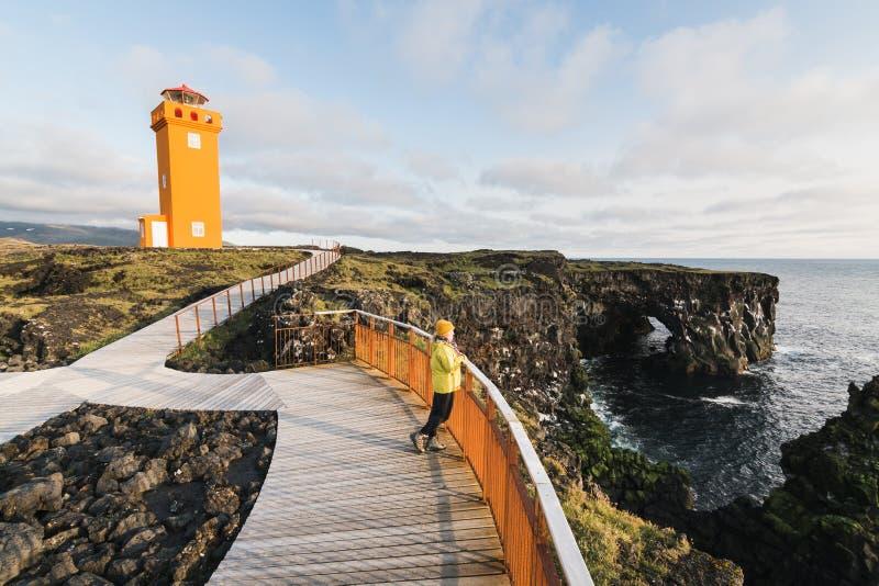 SNAEFELLSNES, mujer en puesta del sol de observación del impermeable amarillo en el faro de Svortuloft, península de Snaefellsnes fotos de archivo libres de regalías