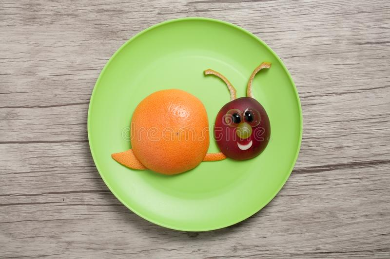 Snail made with fruits on plate and table. Snail made with peach, orange, banana and grape. Amusing way to make fast healthy food for children. Shot with Canon royalty free stock photography