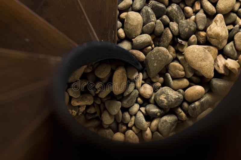 A snail staircase detail from top ascending down to a pool of pebbles. Travel to nature concept. royalty free stock image