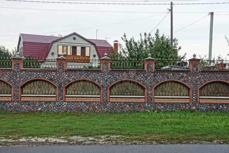 Snak gekleurde omheining van steen en staalstaven met een patroon in het groene gras bij de weg stock fotografie