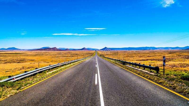 Snak Rechte Weg door het Eindeloze brede open landschap van het semi Gebied van woestijnkaroo in Vrije Staat en Oostelijke Kaappr royalty-vrije stock fotografie
