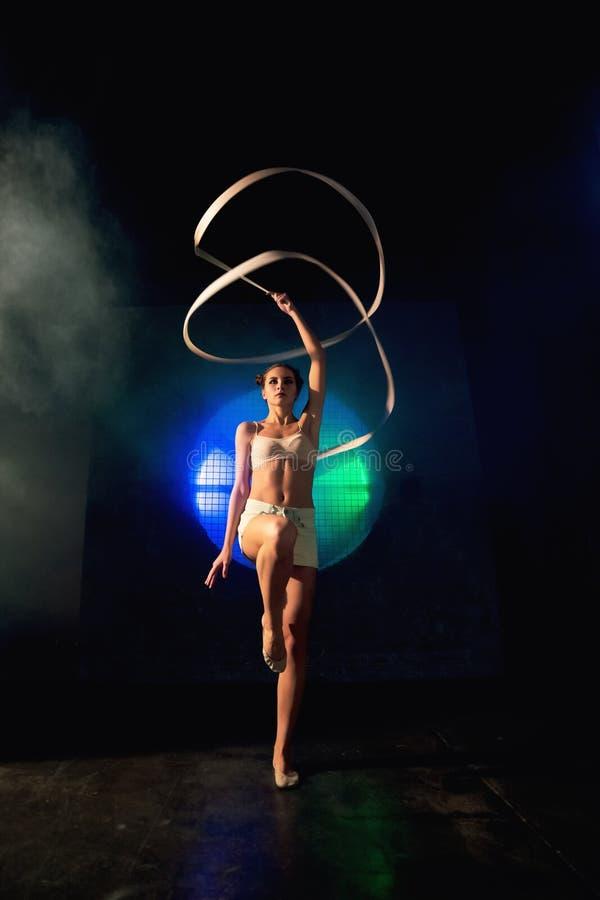 Snak schot van een leuke jonge turnervrouw die met gymnastiekband opleiden stock fotografie