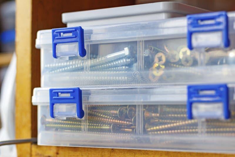 Snak self-tapping schroeven in transparante plastic opslagdoos op de plank in workshop royalty-vrije stock fotografie