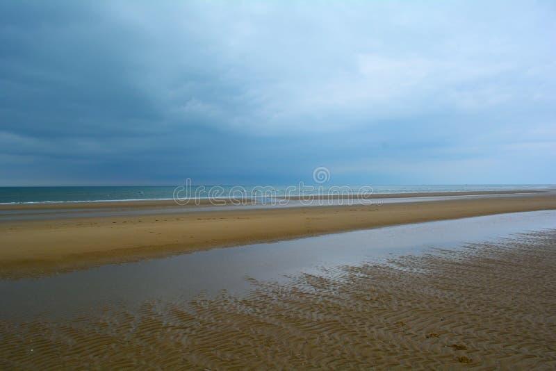 Snak zandig strand van de kust van Norfolk en lage donkerblauwe bewolkte hemel, Noordelijke Overzees, Holkham-strand, het Verenig royalty-vrije stock fotografie