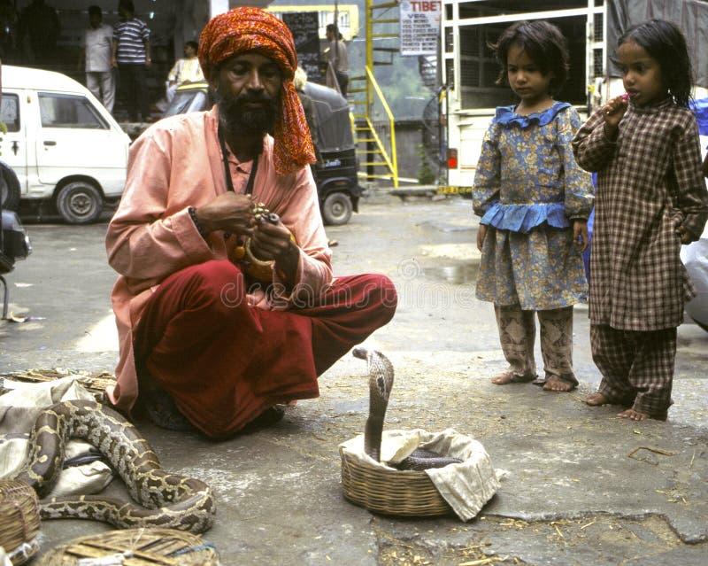Snake Charmer. VASHISHT, INDIA - JULY 2006 - A snake charmer draws a crowd with his cobras in baskets in Uttar Pradesh stock image