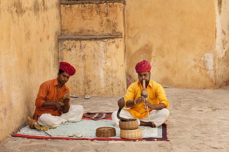 Snake charmer. JAIPUR, INDIA - APRIL 22, 2015: A snake charmer is playing the flute for the cobra sitting by the wall in the Fort Amber on April 22, 2015 in stock photo